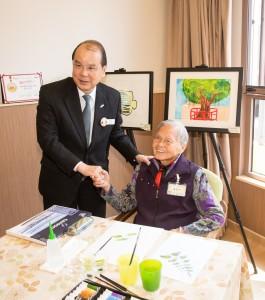 综合中心94岁高龄的院友黄玉少婆婆(右)向政务司司长张建宗GBS太平绅士(左)介绍其画作。