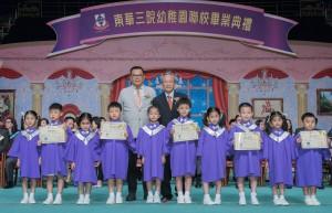 东华三院主席兼校监李鋈麟博士太平绅士(左)陪同主礼嘉宾香港大学教育学院谢锡金教授(右)颁发毕业证书予幼稚园毕业学生代表。