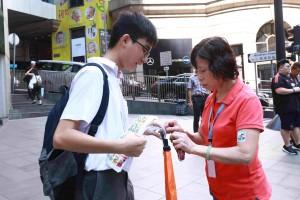图十一为志愿者积极鼓励市民捐款买旗外,更落力介绍互动游戏「东华三院X Hello Wong爱‧邮你Action」,吁买旗的市民创作明信片并写上祝福语或心意字句,以创意传扬关爱的讯息。