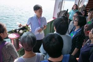 参加者细心聆听职员讲解环保海葬仪式。