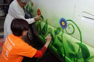 市民在艺术家带领下在老爷车车身上进行创作。