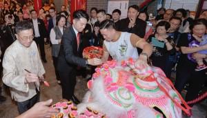 东华三院主席王贤志先生(中)与各位嘉宾为醒狮点睛挂红。