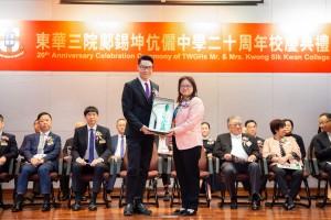 图二为东华三院主席兼名誉校监王贤志先生(左)致送纪念品予主礼嘉宾教育局新界区首席教育主任陈展桓女士(右)。