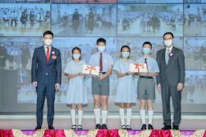 图一为东华三院主席兼名誉校监谭镇国先生(左一)陪同主礼嘉宾教育局局长杨润雄太平绅士(右一)颁发毕业证书予毕业学生代表。